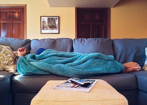 persoon op de bank onder de dekens